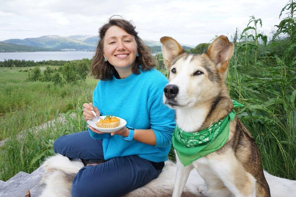 Ei jenta sitter ved siden av en hund og spiser kake